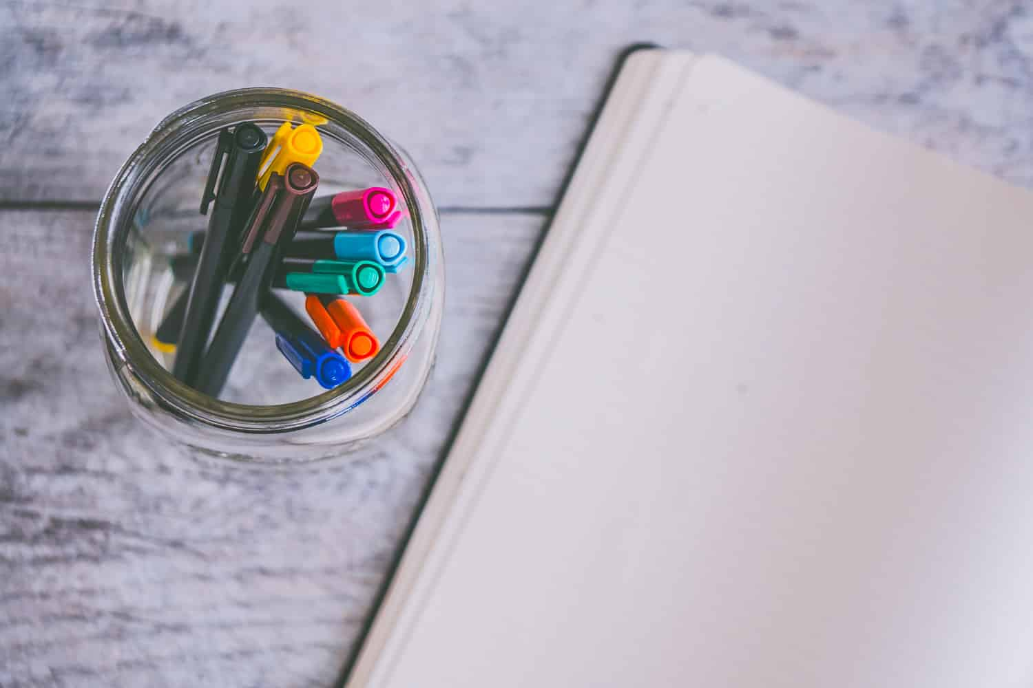 A jar of markers sits beside an open notebook, inviting the user to begin the self-editing process.