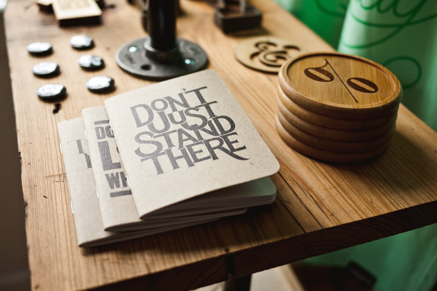 "Books entitled ""Don't Just Stand There!"" are stacked on a wooden table."