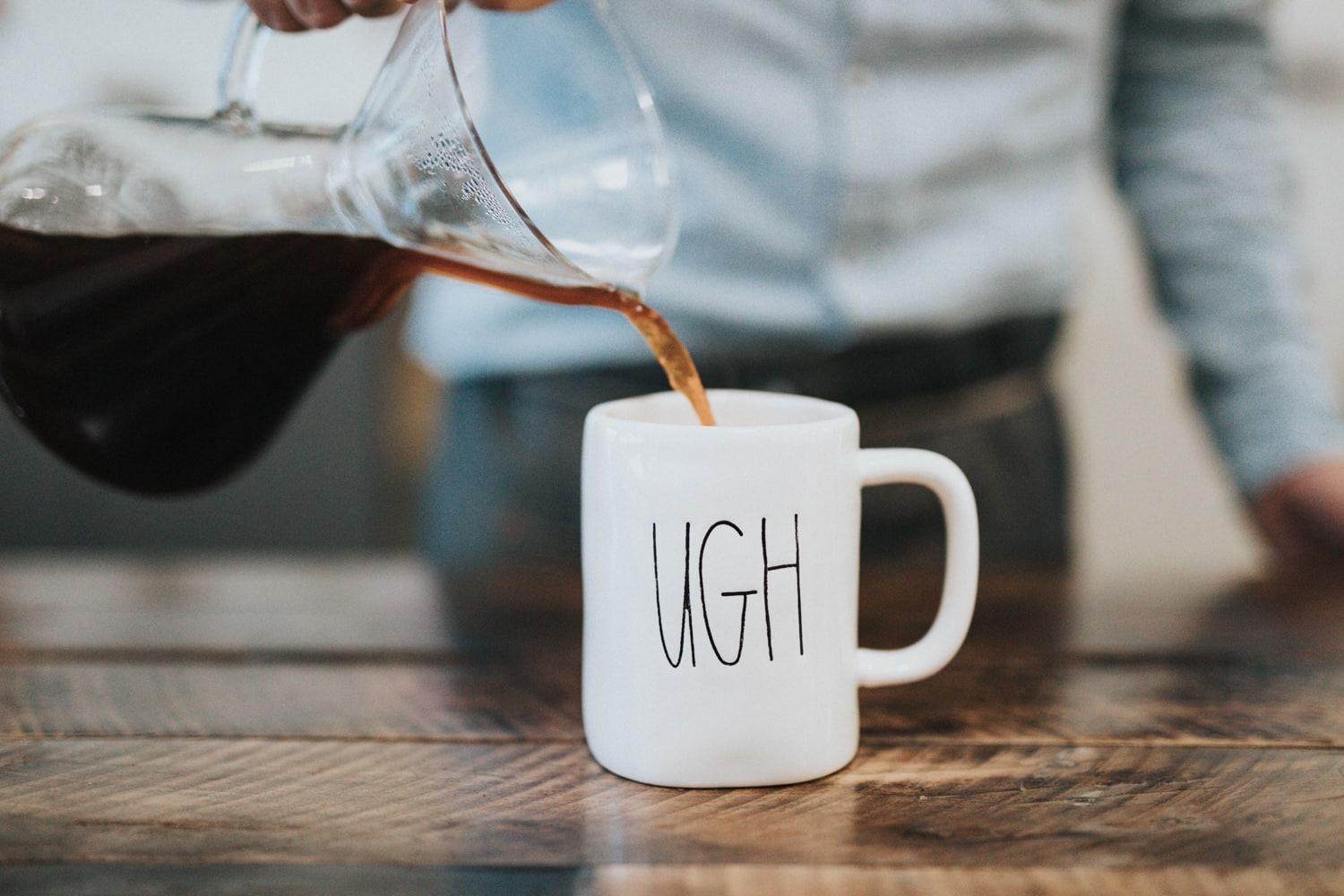 "A man pours coffee into a mug labeled ""Ugh"" while thinking about building an About Me page."