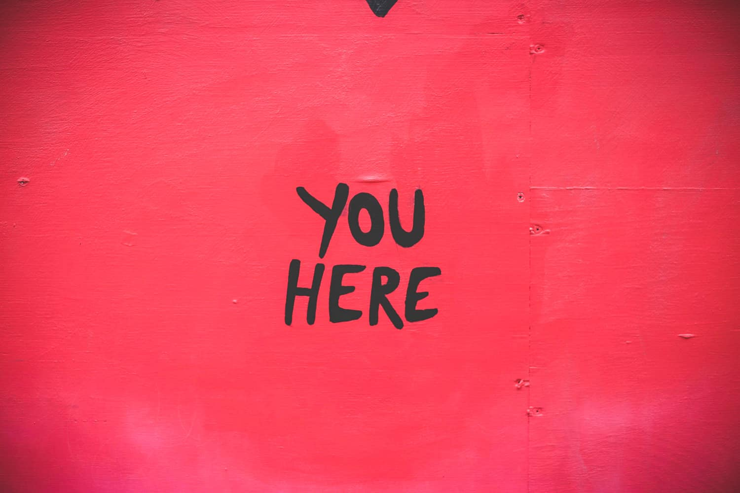 "The words ""You Here"" are painted on a red wall."